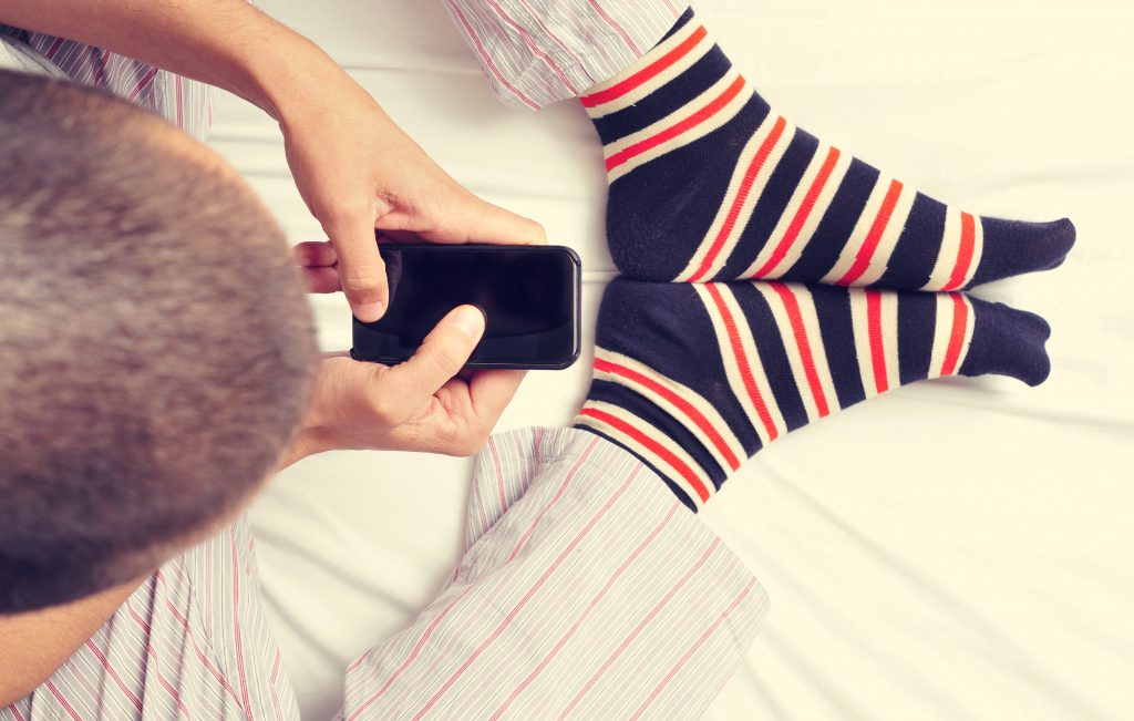 young man using a smartphone in bed